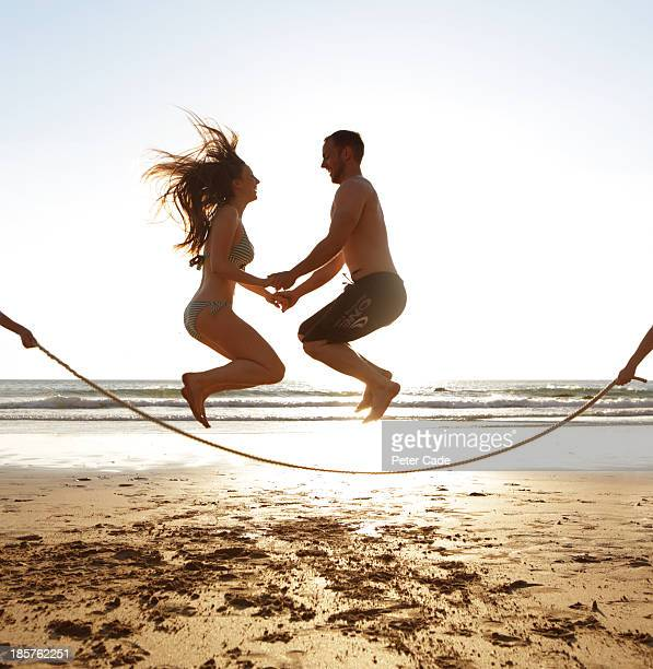 Young couple jumping over skipping rope