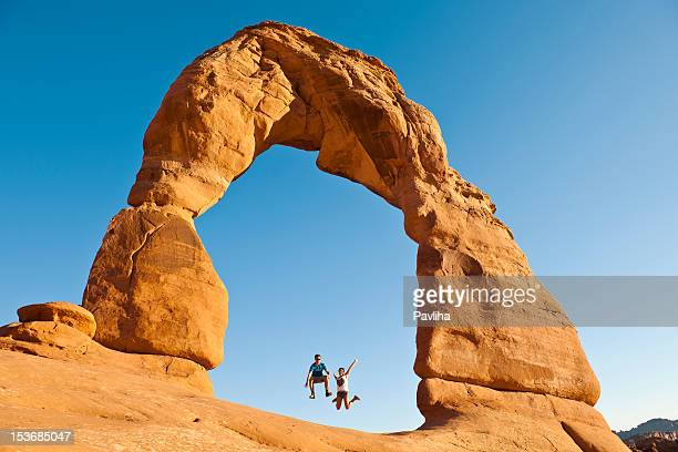 young couple jumping under delicate arch utah usa - delicate arch stock pictures, royalty-free photos & images