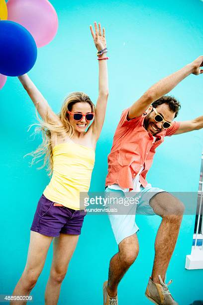 Young couple jumping with joy holding balloons