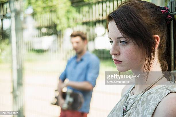Young couple keeping distance in park after argument
