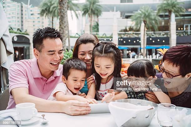 Young couple, kids & grandma using smartphone