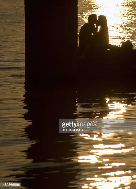 A young couple kiss at sunset on the Danube river in Vienna on August 3 during a hot summer night AFP PHOTO / JOE KLAMAR
