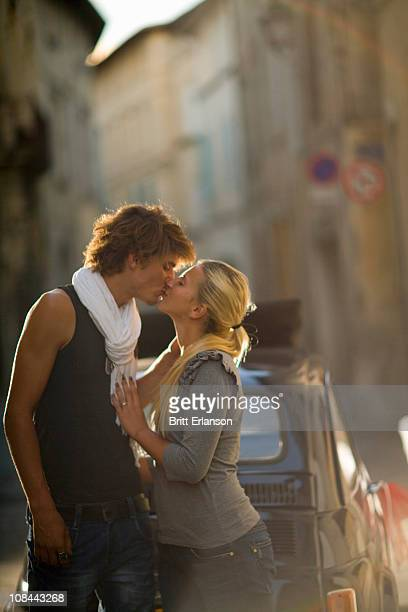 Young couple kiss in sunset street