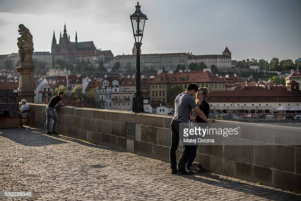 A young couple kiss on the Charles Bridge on May 9 2016 in Prague Czech Republic The Charles Bridge construction began in 1357 by Charles IV's...