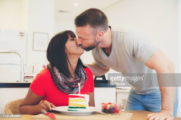 Young Couple Kisses Each Other Before Cutting their Anniversary Cake
