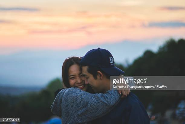 Young Couple Kissing Against Sky During Sunset