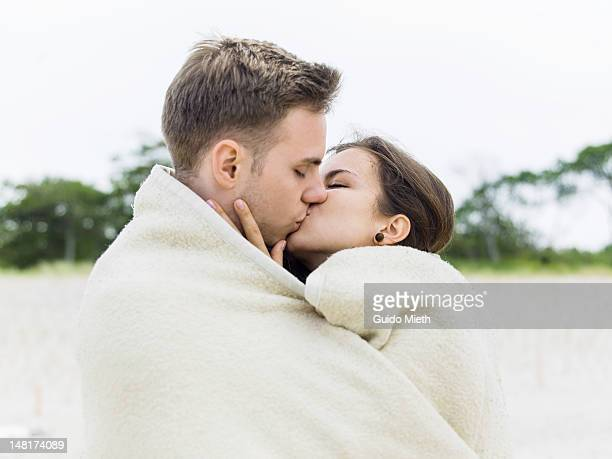 young couple kissing at the beach - kissing on the mouth stock photos and pictures