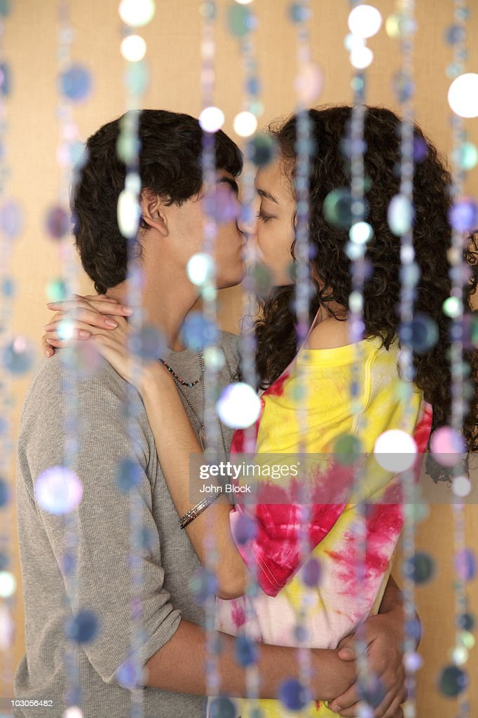 Young couple kissing behind screen : Stock Photo