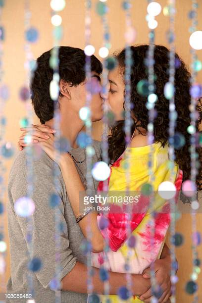 young couple kissing behind screen - indian girl kissing stock photos and pictures