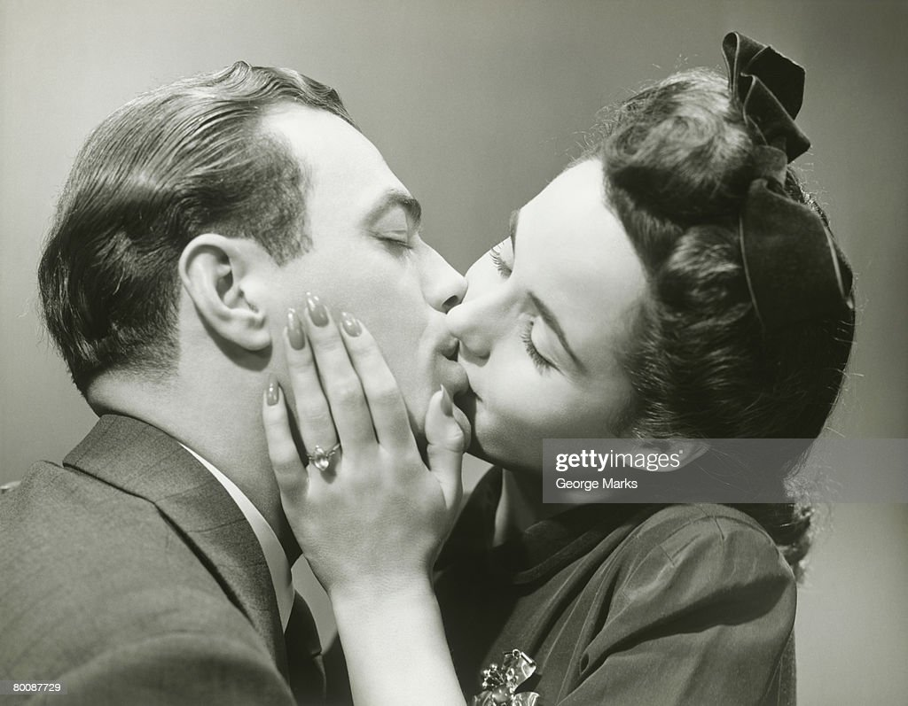 Young couple kissing, close-up, studio shot : Stock Photo