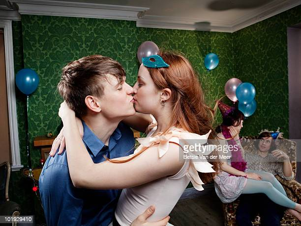 young couple kissing eachother at party.