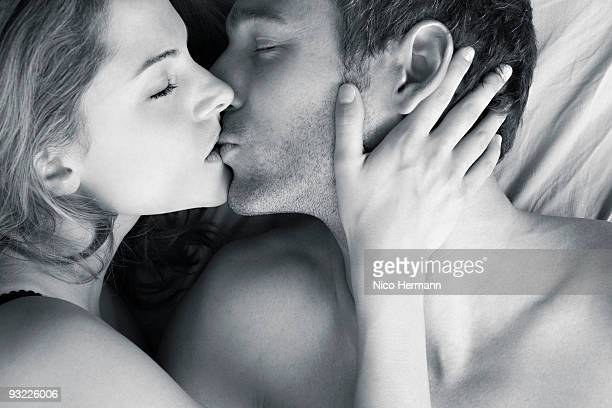 Couple kissing in bed, elevated view