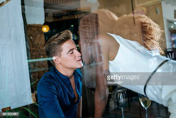 Young couple kissing in a bar seen from behind window