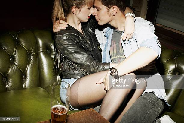 young couple kissing in a sofa - leg kissing stock photos and pictures