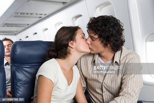 Young couple kissing in airplane
