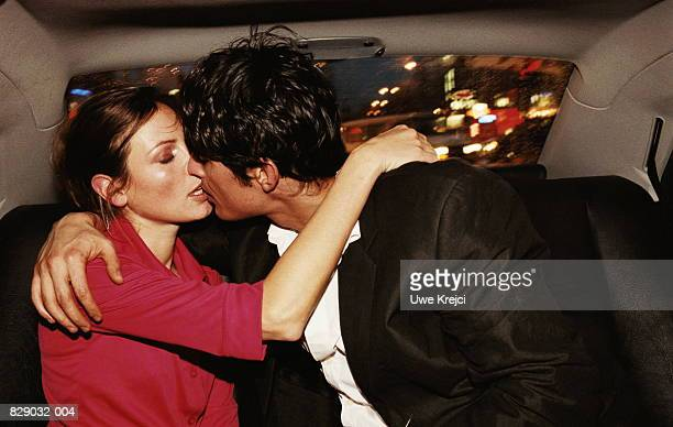 young couple kissing in back of car, close-up - kiss stock pictures, royalty-free photos & images