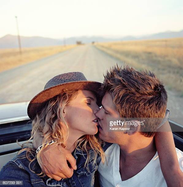 young couple kissing in back of convertible, close-up - kissing on the mouth stock photos and pictures