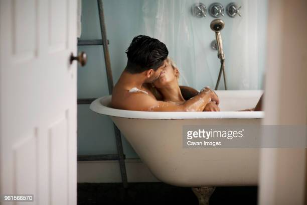 young couple kissing in bathtub at home - couples showering stock pictures, royalty-free photos & images