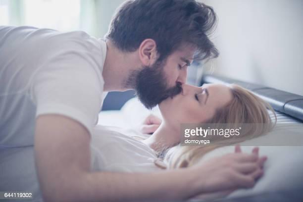 jong koppel kussen in bed - verliefd worden stockfoto's en -beelden
