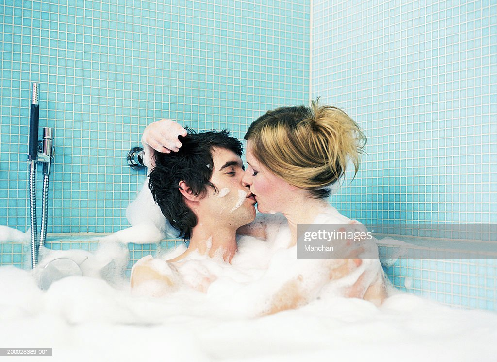 Young couple kissing in bubble bath : ストックフォト