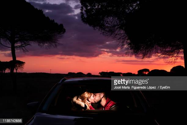 young couple kissing in car during sunset - kissing stock pictures, royalty-free photos & images