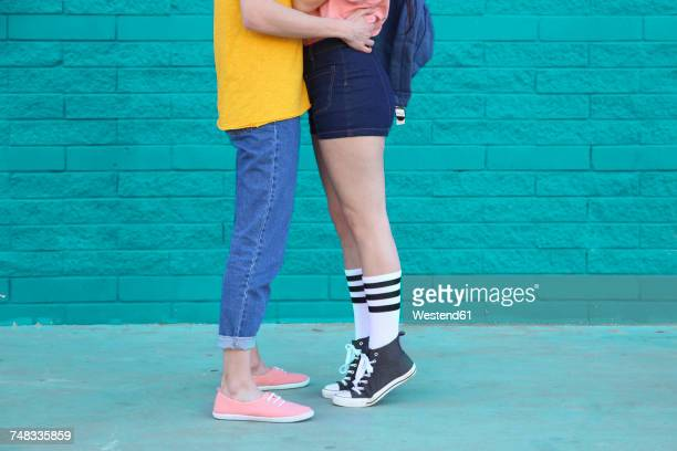 young couple kissing in front of blue brick wall, partial view - leg kissing stock photos and pictures