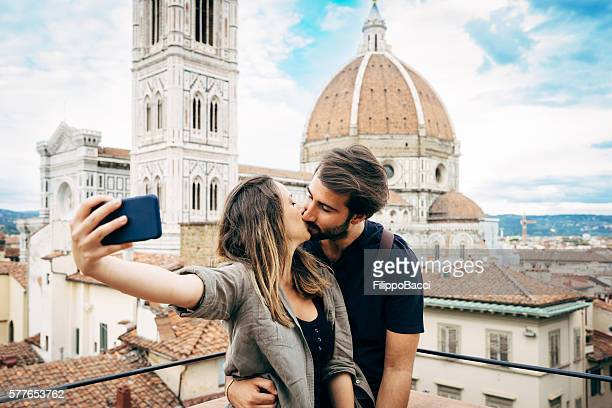 young couple kissing in front of florence's cathedral - florence italy foto e immagini stock