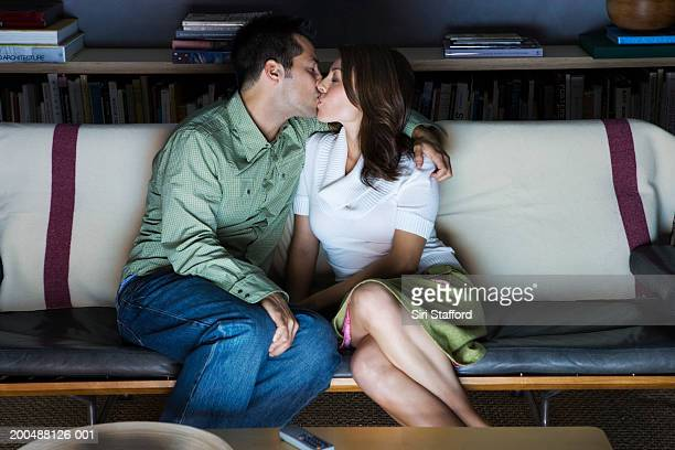 Young couple kissing in front of television