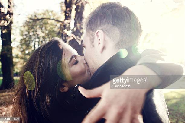 young couple kissing in park - kissing on the mouth stock photos and pictures