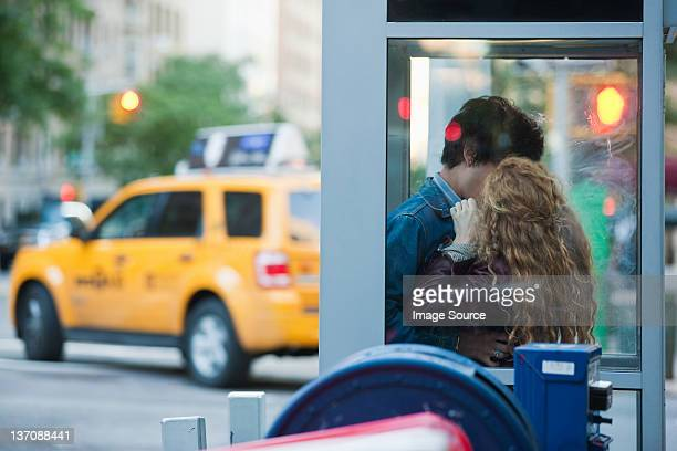 Young couple kissing in telephone booth