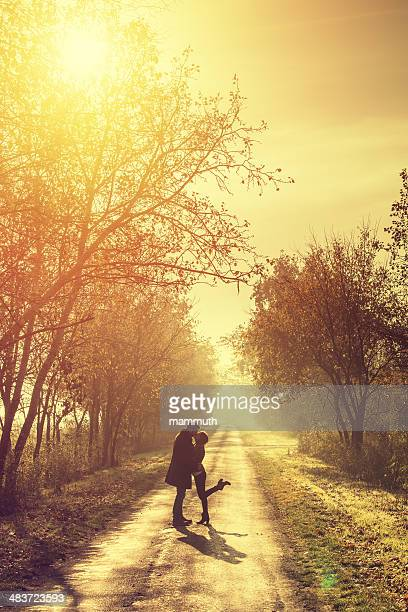 young couple kissing in the autumn sunshine