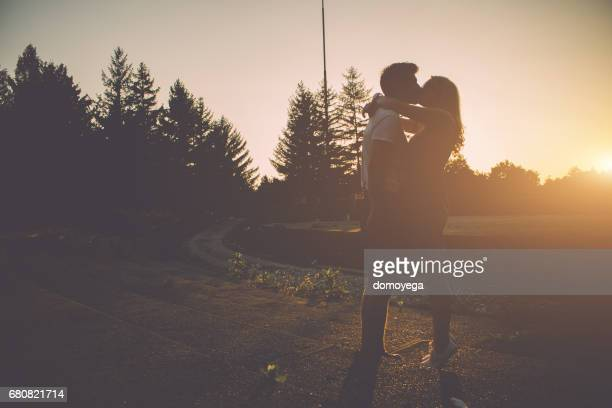 Young couple kissing on a beautiful summer day in the sunset