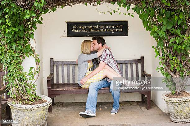 """a young couple kissing on a bench - """"compassionate eye"""" stock pictures, royalty-free photos & images"""