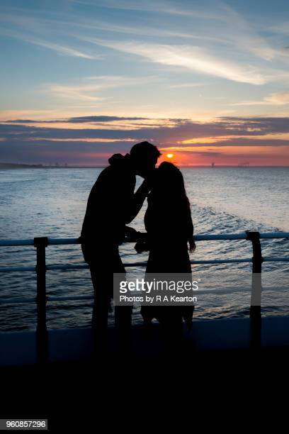young couple kissing on a seaside pier at sunset - saltburn stock photos and pictures