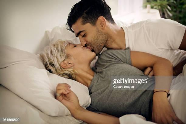 young couple kissing on bed at home - embrasser sur la bouche photos et images de collection