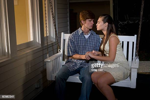 Young couple kissing on porch swing