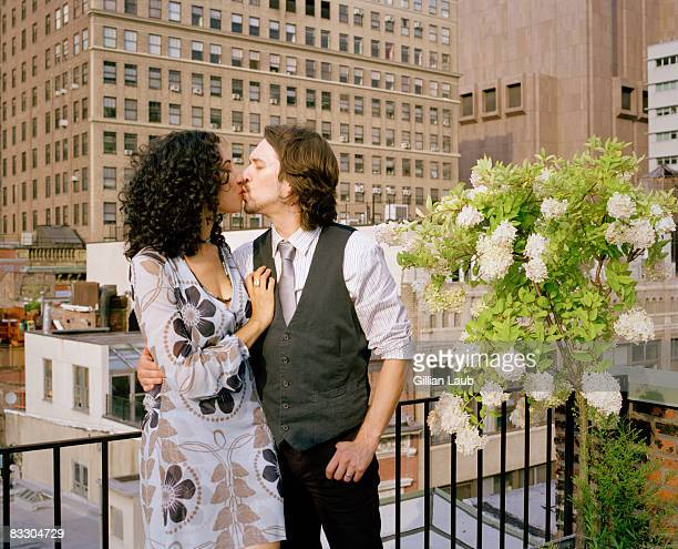 Young couple kissing on rooftop at family reunion.