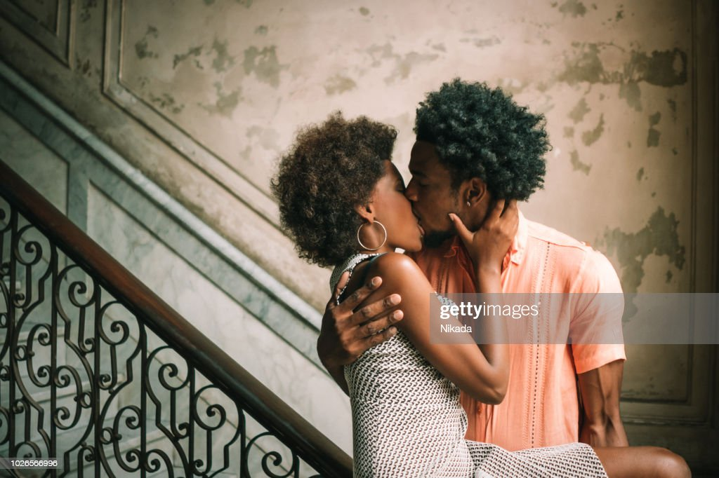 Young Couple kissing on steps against wall, Havana, Cuba : Stock Photo
