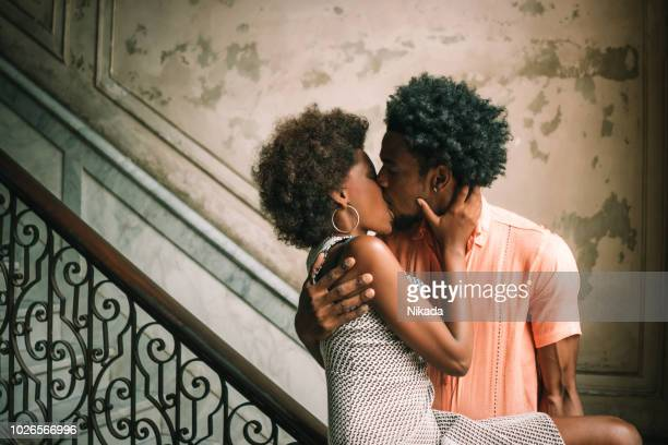 Young Couple kissing on steps against wall, Havana, Cuba