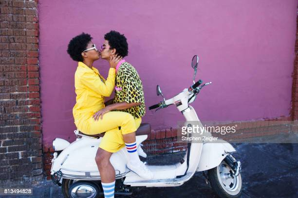 young couple kissing on the back of a scooter - kiss stock pictures, royalty-free photos & images
