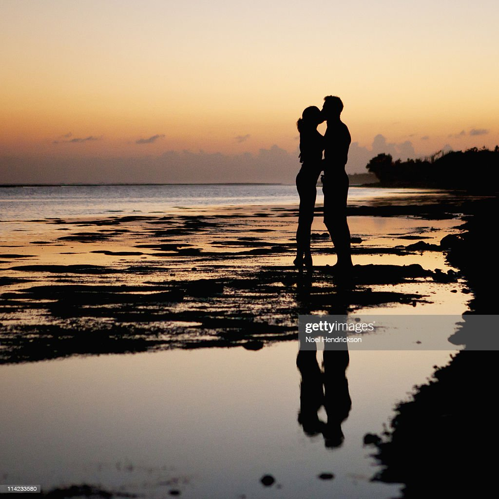 Young Couple Kissing On The Beach At Sunset Stock Photo