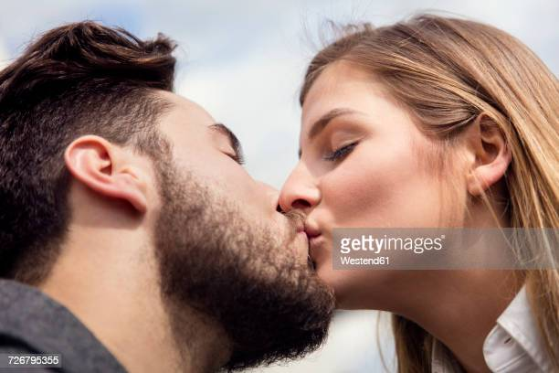 young couple kissing - kissing on the mouth stock photos and pictures