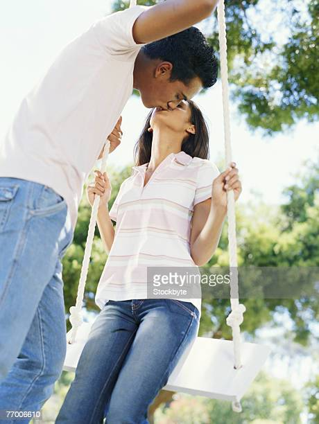 Young couple kissing sitting on swing