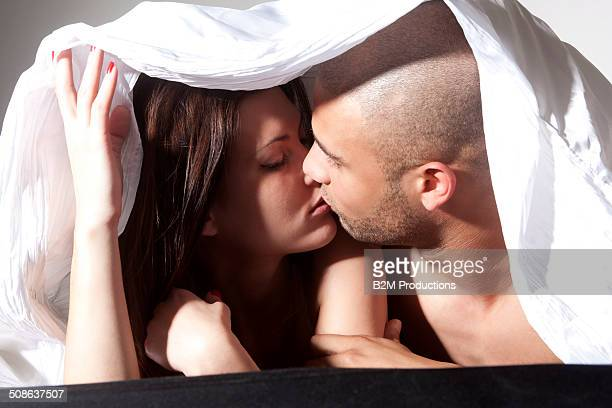 Young Couple Kissing Under Bedsheet