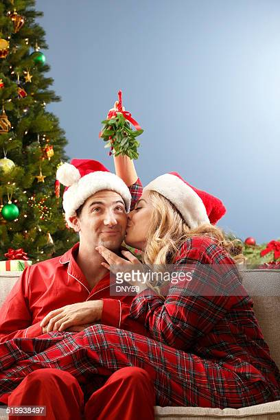 young couple kissing under mistletoe - mistletoe stock photos and pictures