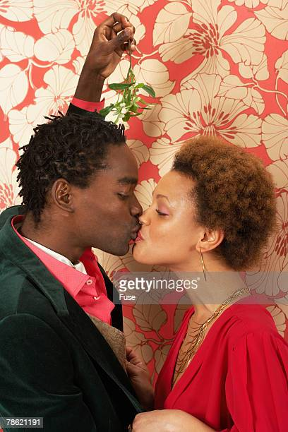 Young Couple Kissing Under Mistletoe