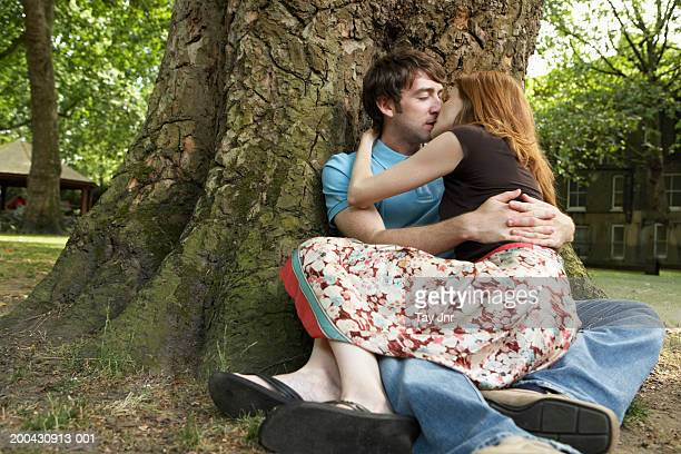 young couple kissing under tree, rear view of woman - bacio sulla bocca foto e immagini stock