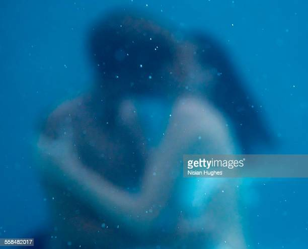 Young couple kissing underwater with soft focus