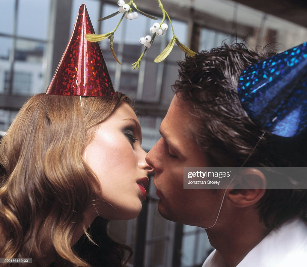 Young couple kissing, wearing party hats, close-up : Photo