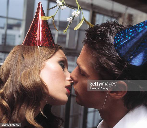 young couple kissing, wearing party hats, close-up - gui photos et images de collection